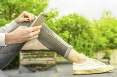 Manos de una muchacha con un teléfono móvil Fotos de archivo libres de regalías