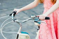 Manos de una muchacha en el manillar de la bicicleta Fotos de archivo libres de regalías