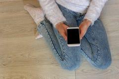 Manos de una muchacha que sostiene un teléfono móvil teléfono innovador de los adolescentes Fotos de archivo libres de regalías