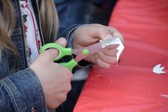 Manos de una muchacha que talla el papel para los artes Fotos de archivo libres de regalías