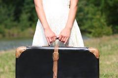 Manos de una mujer con una maleta Fotografía de archivo libre de regalías