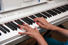 Manos de una mujer joven que juega el piano imágenes de archivo libres de regalías