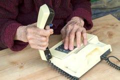 Manos de una mujer mayor con un teléfono pasado de moda Foto de archivo