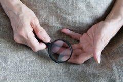 Manos de una mujer mayor que sostiene una lupa imagen de archivo