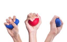 Manos de una mujer que exprime una bola de la tensión Foto de archivo libre de regalías