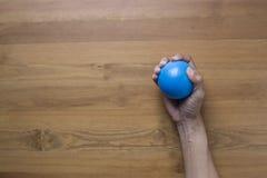 Manos de una mujer que exprime una bola de la tensión en la tabla Imagenes de archivo
