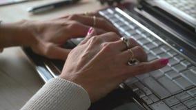 Manos de una mujer que mecanograf?a un ordenador almacen de metraje de vídeo