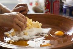 Manos de una mujer que mezclan los ingredientes como los huevos crudos, harina, polvo B foto de archivo