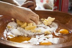 Manos de una mujer que mezclan los ingredientes como los huevos crudos, harina, polvo B fotos de archivo