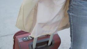 Manos de una mujer que sostiene una maleta por la manija Una mujer camina con una maleta al edificio del aeropuerto Un negocio almacen de video