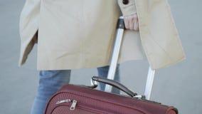 Manos de una mujer que sostiene una maleta por la manija Una mujer camina con una maleta al edificio del aeropuerto Un negocio metrajes