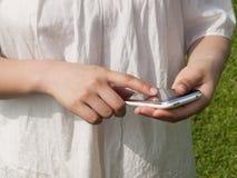 Manos de una mujer que usa el teléfono móvil Imagenes de archivo
