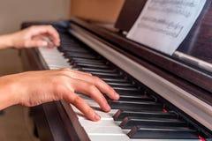 Manos de una niña que juega el piano Fotografía de archivo libre de regalías
