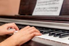 Manos de una niña que juega el piano Imágenes de archivo libres de regalías