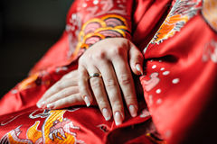 Manos de una novia en un traje rojo con un anillo de bodas en su finger Foto de archivo