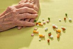 Manos de una señora mayor con la medicación Fotografía de archivo libre de regalías