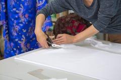 Manos de una tela del corte de la costurera Foto de archivo libre de regalías