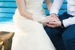 Manos del abarcamiento de novia y del novio Imagen de archivo