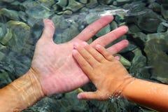 Manos del adulto y de los niños que sostienen el submarino Foto de archivo