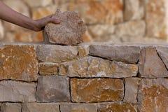 Manos del albañil que trabajan en la pared de piedra de la albañilería Fotografía de archivo