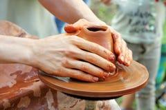 Manos del alfarero en el pote de arcilla de la rueda de la cerámica Imagenes de archivo