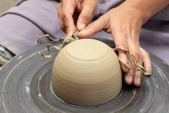 Manos del alfarero que muelen el tazón de fuente de la arcilla Foto de archivo libre de regalías