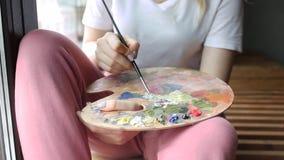 Manos del artista con colores de mezcla del cepillo en cierre de la paleta para arriba Arte, creatividad, afici?n almacen de metraje de vídeo