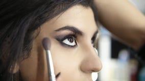 Manos del artista de maquillaje profesional que aplica el sombreador de ojos al ojo modelo del ` s usando cepillo especial Bellez almacen de metraje de vídeo