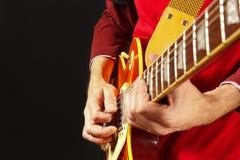 Manos del artista que tocan la guitarra eléctrica en fondo oscuro Fotos de archivo