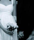 Manos del asimiento de novia y del novio; La novia sostiene el ramo Imagen de archivo libre de regalías
