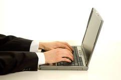 Manos del asunto en la computadora portátil Foto de archivo libre de regalías