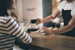 Manos del barista que ponen el jarro del café en el contador de la barra imagen de archivo libre de regalías