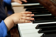 Manos del bebé que juegan el piano Fotografía de archivo libre de regalías