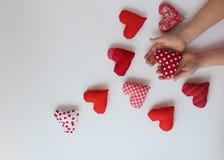 Manos del bebé que llevan a cabo pequeños corazones rojos Fotos de archivo