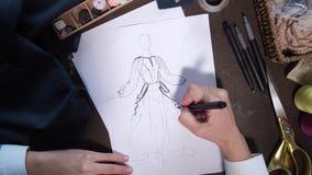 Manos del bosquejo del dibujo del diseñador de ropa del vestido metrajes