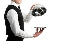 Manos del camarero con la tapa del cloche Fotografía de archivo