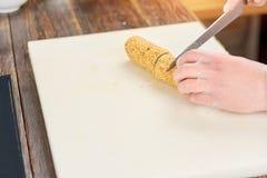Manos del cocinero con el rollo de sushi del corte del cuchillo Imagen de archivo libre de regalías