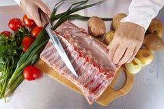 Manos del cocinero con la carne cruda Imagenes de archivo
