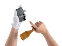 Manos del cocinero con la espátula y el smartphone, compra de la cocina en Fotos de archivo