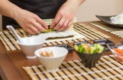 Manos del cocinero de la mujer que ruedan encima de un sushi japonés Foto de archivo