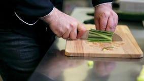 Manos del cocinero de sexo masculino que tajan el pepino en cocina metrajes