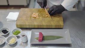 Manos del cocinero en el uniforme blanco del restaurante que corta pequeños pescados de color salmón almacen de video