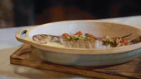 Manos del cocinero en los guantes de goma blancos que ponen verduras cutted en aceite de oliva en el cierre cocinado de los pesca almacen de metraje de vídeo