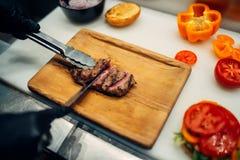 Manos del cocinero en pedazo jugoso del filete de los cortes de los guantes imagen de archivo libre de regalías