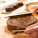 Manos del cocinero en torta de extensión de la acción Fotografía de archivo libre de regalías