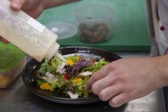 Manos del cocinero, preparando una ensalada con el pollo fotos de archivo libres de regalías