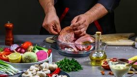 Manos del cocinero que cocinan la carne del conejo con las verduras en fondo de madera oscuro Concepto del alimento Foco selectiv imágenes de archivo libres de regalías