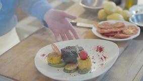 Manos del cocinero que empuja lejos la placa con el cocido al vapor de la verdura al vapor en el cierre de la tabla para arriba L almacen de video