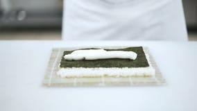 Manos del cocinero que ponen la salsa y el pepino en el arroz que hace el sushi almacen de metraje de vídeo