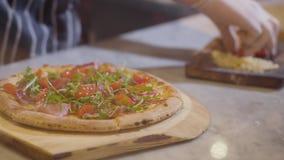 Manos del cocinero que ponen los ingredientes en la pizza que miente en un cierre del tablero de madera para arriba Cocinar la pi almacen de metraje de vídeo